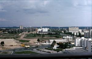 Blick aus dem noch im Bau befindlichen Tor-Hochhaus am Loschwitzer Weg. Im Hintergrund sieht man schon die Bautätigkeit am Blasewitzer Ring. Von den Bauten an der Obstallee und vom Staaken-Center ist noch nichts zu sehen. Im Vordergrund sieht man das Flachdach des Einkaufscenters der Wissell-Siedlung
