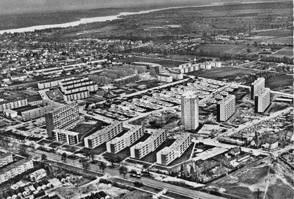 Eine Postkarte von 1965 zeigt die Bebauung südlich der Heerstraße: Mitte links das Laubenganghochhaus mit den Maisonettewohnungen von Norman Braun. Im Vordergrund sieht man noch die letzten Behelfsunterkünfte, die sog. Nissenhäuser.