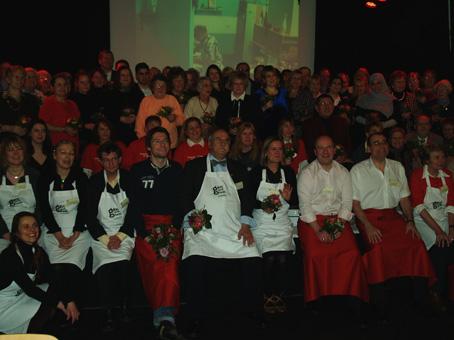 Auf der Bühne die ehrenamtlichen Ehrengäste - am Bühnenrand mit Schürzen das Küchen- und Servicepersonal