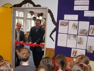 Mit Hilfe der Stadträte Hanke und Röding durchschneidet Bernd Jaeke (Schulleiter) das Band zur neugestalteten Bibliothek